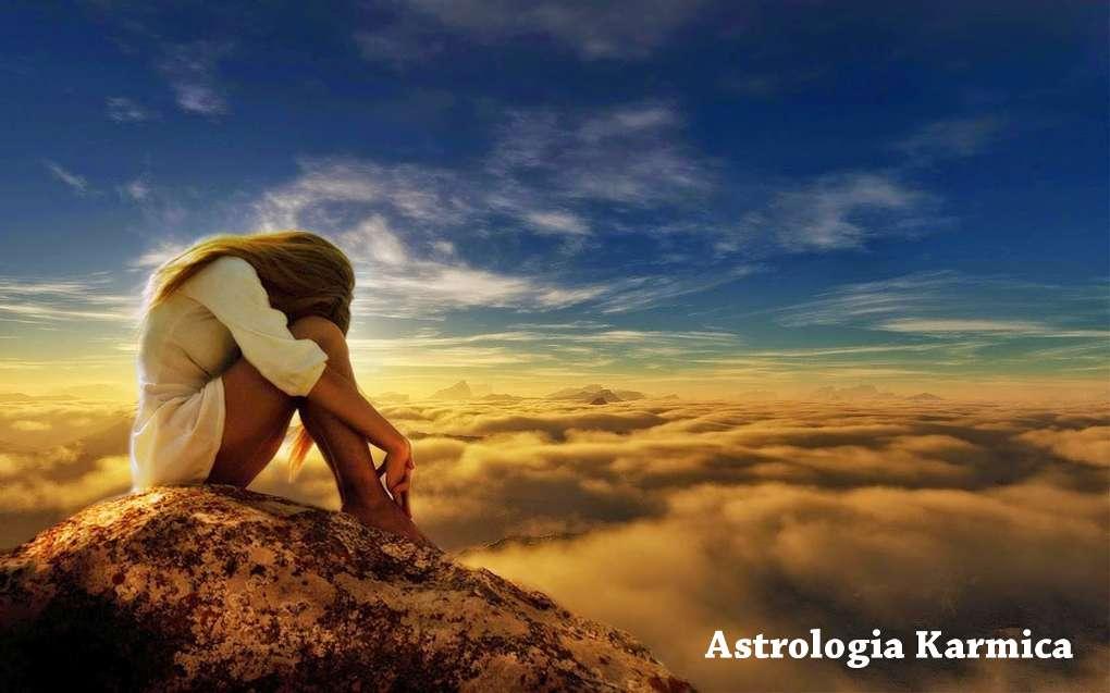 Conosci te stesso e migliora con l'Astrologia Karmica. Nell'immagine una giovane donna è su un monte al di sopra delle nuvole.